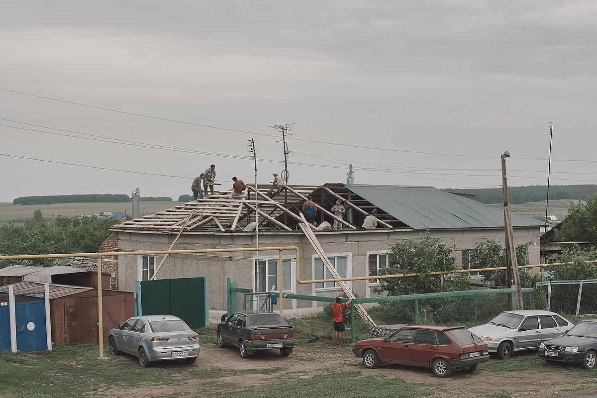 Season workers repairing the roof in the Balkans village.