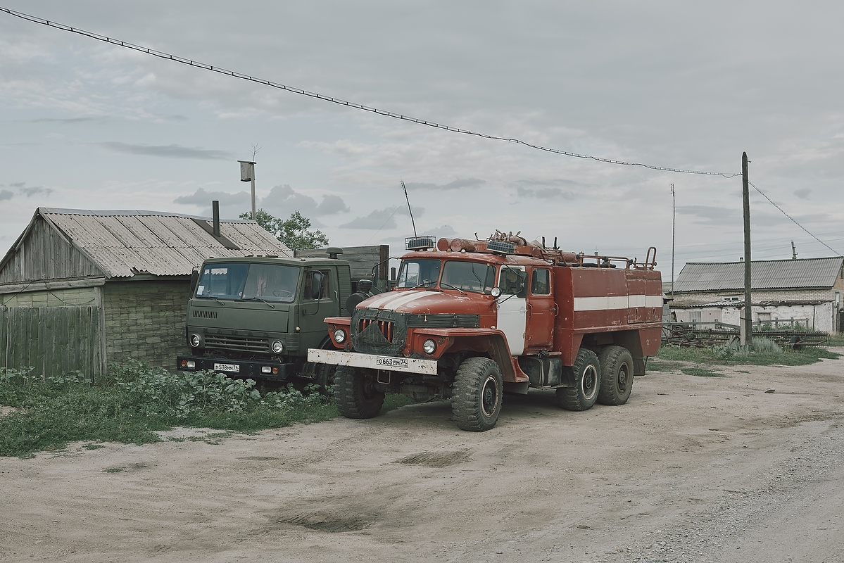 A truck and a firetruck in the Warsaw village.