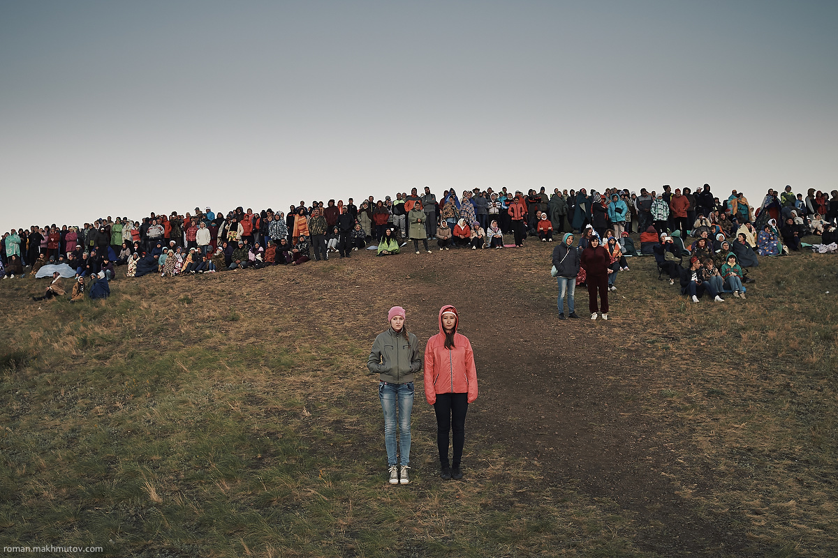 People are waiting for the sunrise on the so-called Shaman Hill, Arkaim, Russia.